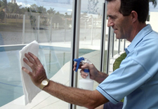 an image of someone cleaning glass easily beacue he used a glass treatment we sell